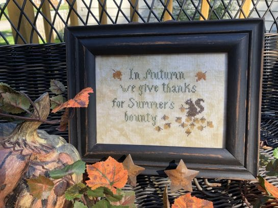 Photo of finished sampler from Autumn Smalls set by Falling Star Primitives, displayed on wicker bench with Autumn leaves