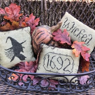 Photo of finished Bewitched pillow tuck set in a wire basket filled with Autumn leaves and other Fall season decor