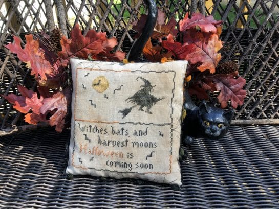 Photo of finished Coming Soon pillow tuck by Falling Star Primitives, sitting on wicker bench against leaves and ceramic black cat