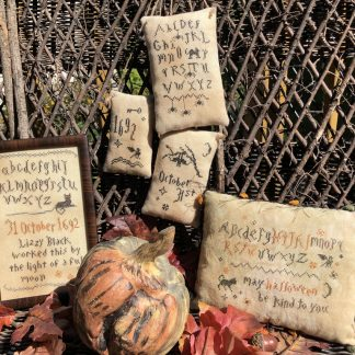 Photo of finished Wicked Little Samplers set by Falling Star Primitives, displayed against a wood screen with Autumn leaves and other Fall seasons decor