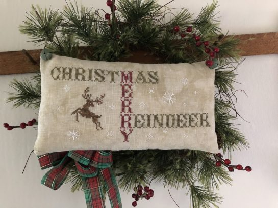 Photo of finished pillow tuck from Christmas Merry Reindeer by Falling Star Primitives, displayed hanging on wall on top of evergreen branches