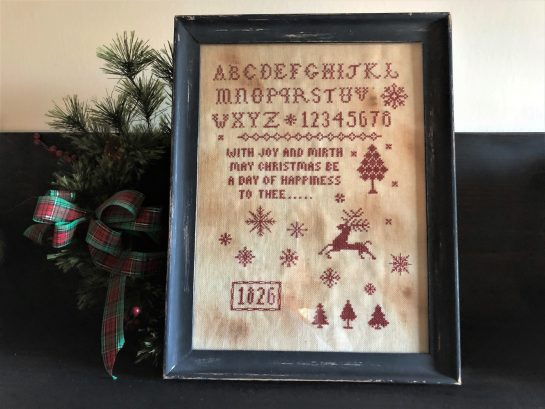 Photo of finished sampler from Joy & Mirth Redwork Sampler by Falling Star Primitives, displayed on top of evergreen branches on shelf