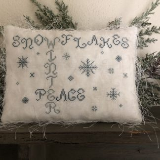 Photo of finished pillow tuck from Snowflakes by Falling Star Primitives, displayed on top of evergreen branches