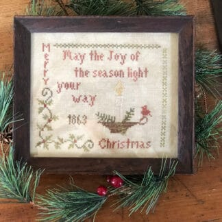 Photo of finished sampler from Light Your Way Sampler by Falling Star Primitives, displayed on top of evergreen branches