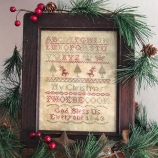 Photo of finished sampler from Phoebes Christmas by Falling Star Primitives, displayed on top of evergreen branches on shelf